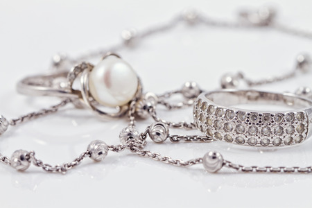 diamond necklace: Silver ring with precious stones and pearl are together with a silver chain on acrylic