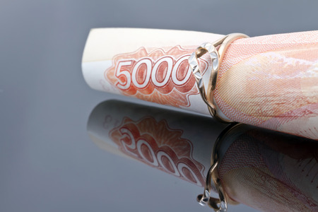 financial planning married: gold ring dressed on the banknote 5000 rubles