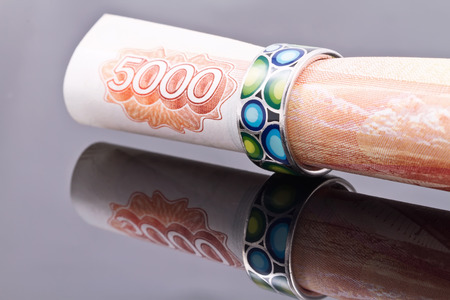 financial planning married: Silver ring with colored enamel put on a banknote 5000 rubles