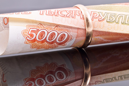 financial planning married: gold wedding ring is worn on the banknote 5000 rubles
