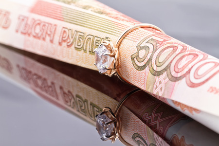 financial planning married: gold ring with diamond put on a banknote 5000 rubles