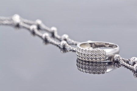 fine silver: engagement silver ring with precious stones and fine silver chain Stock Photo
