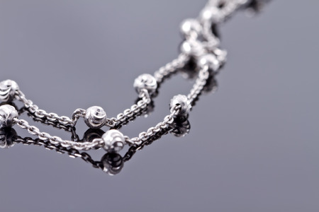 silver backgrounds: Elegant unusual silver chain on the reflecting surface