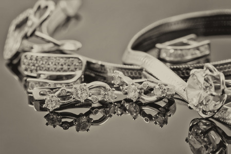 reflectance: gold ring, earrings and chains on a reflective surface