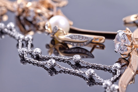 Elegant unusual silver chain and gold jewerly on the reflecting surface