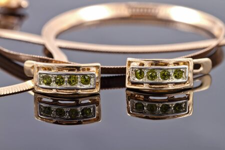 sumptuousness: Beautiful and elegant gold earrings with emeralds against other gold jewelry