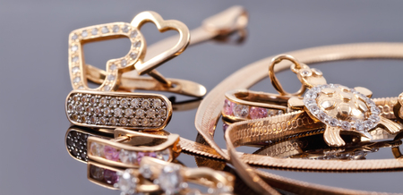 pedant: A variety of jewelry on the reflecting surface: the earrings of different styles, chains, rings and a pendant in the shape of turtles Stock Photo