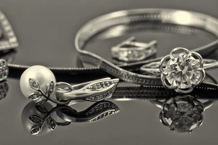 Anillo de oro, pendientes y cadenas en una superficie reflectante Foto de archivo - 44432118