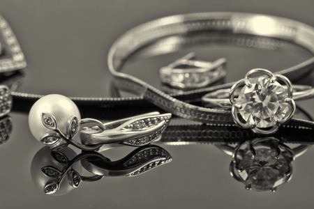 gold ring, earrings and chains on a reflective surface