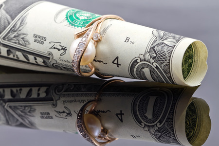 financial planning married: gold ring with pearl dressed on the banknote one dollar