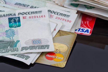 mastercard: VOLGOGRAD - AUGUST 16: Plastic card payment systems Visa and MasterCard are with a bunch of Russian money . August 16, 2015 in Volgograd, Russia. Editorial