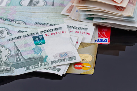 plastic money: VOLGOGRAD - AUGUST 16: Plastic card payment systems Visa and MasterCard are with a bunch of Russian money . August 16, 2015 in Volgograd, Russia. Editorial