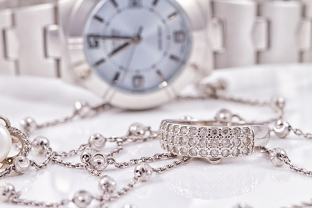 diamond necklace: Silver ring and chain on the background of womens watches Stock Photo