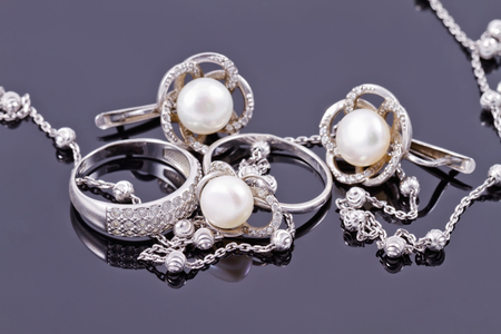 Fine silver rings are together with unusual silver chain on a white acrylic Board