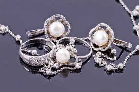 Feine silberne Ringe sind mit ungewöhnlichen Silber-Kette auf einem weißen Acrylbrett Standard-Bild - 45646895