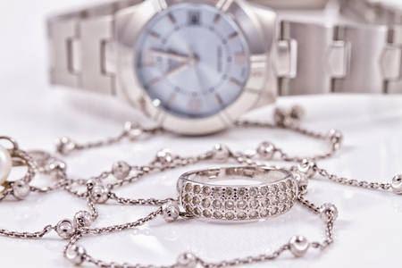 Silver ring and chain on the background of womens watches Stock fotó