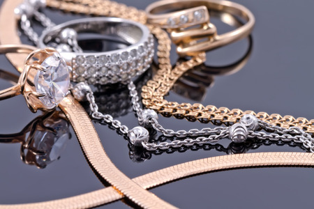 Gold, silver rings and chains of different styles are lying together on the reflecting surface