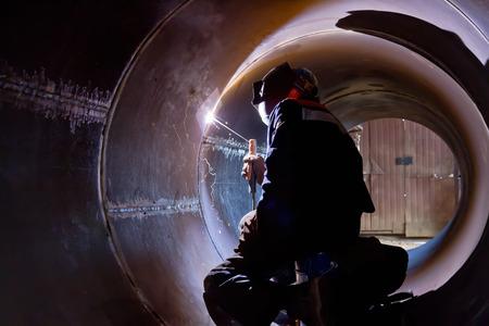 obrero trabajando: La soldadura raíz de la soldadura del soldador desde el interior de la carcasa de aparatos químicos