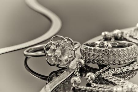 De oro, anillos de plata y cadenas de diferentes estilos están mintiendo juntos en la superficie reflectante Foto de archivo - 46325288