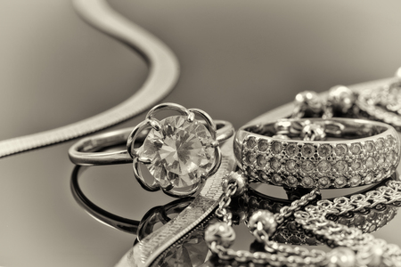Gold, silver rings and chains of different styles are lying together on the reflecting surface Stok Fotoğraf - 46325288