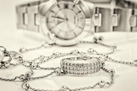 Silberring und Kette auf dem Hintergrund von Damenuhren Standard-Bild - 46325306