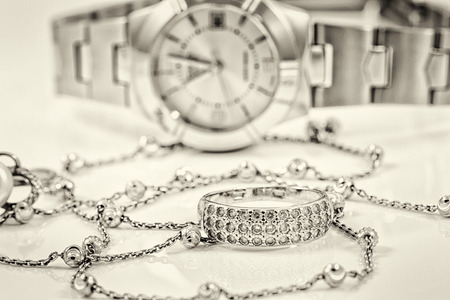 black and silver background: Silver ring and chain on the background of womens watches Stock Photo