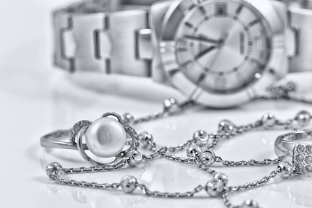 silver ring: Silver ring and chain on the background of womens watches Stock Photo