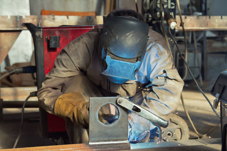 welding mask: Welder in the mask and protective clothing is gaining increased cladding weld Stock Photo