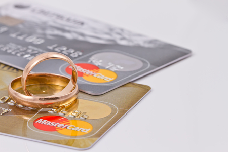 mastercard: VOLGOGRAD - AUGUST 16: Gold wedding rings lie on a two credit cards payment system MasterCard gold  and  MasterCard silver
