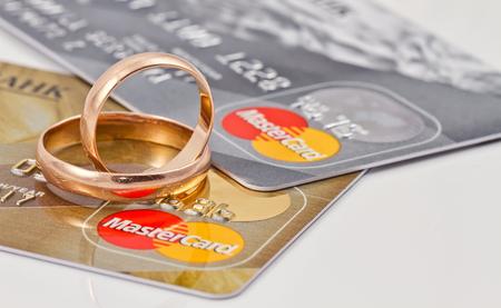 tarjeta de credito: VOLGOGRAD - 16 de agosto: los anillos de bodas del oro se encuentran en un sistema de pago de dos tarjetas de cr�dito MasterCard y MasterCard oro plata