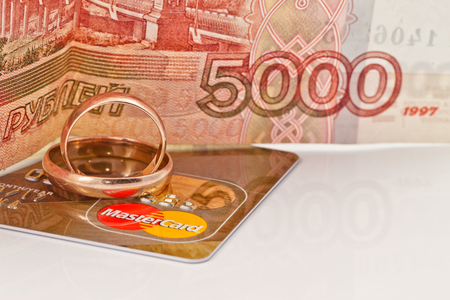 mastercard: VOLGOGRAD - AUGUST 16: Gold wedding rings lie on a credit card payment system MasterCard gold on a background of money. . August 16, 2015 in Volgograd, Russia. Editorial