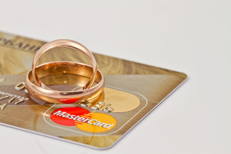mastercard: VOLGOGRAD - AUGUST 16: Gold wedding rings lie on a credit card payment system MasterCard gold Editorial