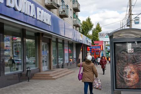 walk board: VOLGOGRAD, RUSSIA - OCTOBER 12: People on the street walk past an information Board Express-Volga Bank exchange rates. Volgograd, 2015