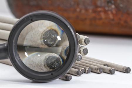 soldadura: Electrodos para la soldadura de arco de mano bajo una mentira lupa en el fondo de la uni�n soldada del tubo de derivaci�n