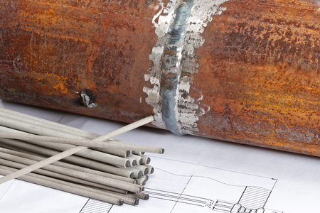 Electrodes for manual arc welding  lie on the background of the welded joint of branch pipe