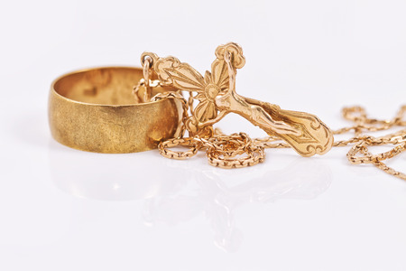 gold cross: engagement gold ring old style and a gold cross on a chain Stock Photo