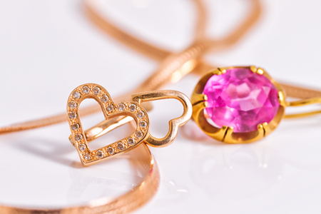 Gold earrings in the shape of a heart and with inset ruby Stock Photo