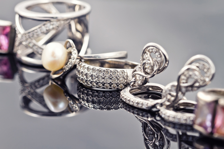 fine silver: Fine silver rings are together with unusual silver chain on a white acrylic Board