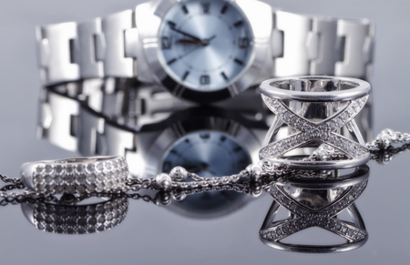 Silver rings of different styles and silver chain on the background of reflections women's watches