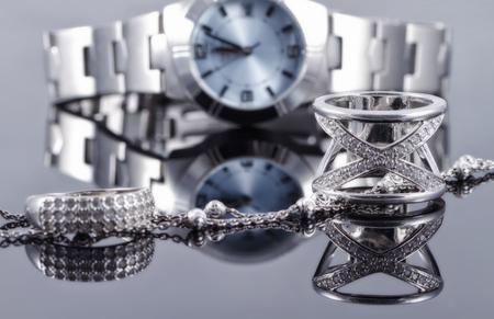 Srebrne pierścienie różnych stylów i srebrny łańcuch na tle refleksji kobiet zegarki