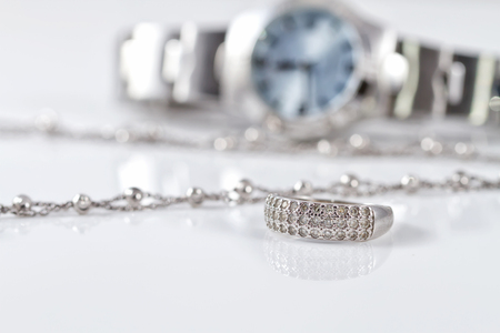 Silver ring and chain on the background of womens watches Banco de Imagens