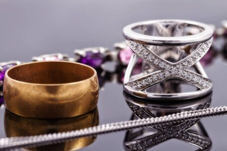 diamond rings: Gold, silver rings and chains of different styles are lying together on the reflecting surface