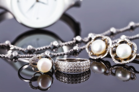 luxe: silver jewelry with pearls on a background of elegant womens watches