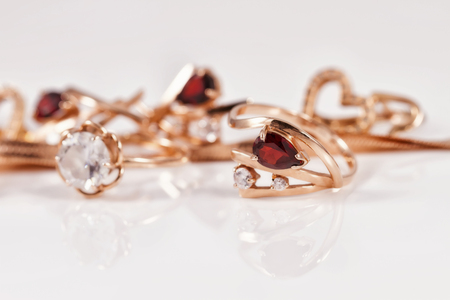 The gold ring is gracefully curved shape ruby against the background of various gold jewelry
