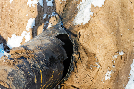 damaged piece of pipe of the main gas pipeline in the trench