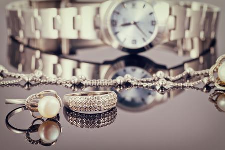 Eleganter Ring aus Silber und Silberkette liegt im Hintergrund der Damenuhren Standard-Bild - 53635183