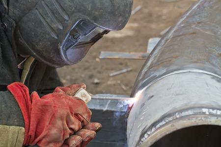fabricator: welder performs welding works on pipelines stainless steel Stock Photo