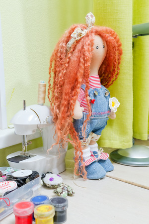 collectible: Collectible doll handmade with red natural hair is on the desktop of the wizard surrounded by buttons, fabrics and paints