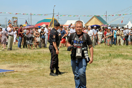hanging around: SMALL CHAPURNIKI, VOLGOGRAD, RUSSIA - MAY 24: Photographer at Sabantui celebrations with two cameras hanging around his neck. May 24, 2014 in Volgograd, Russia.