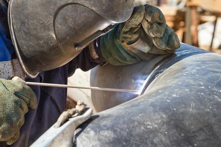 steel works: welder performs welding works on pipelines stainless steel Stock Photo